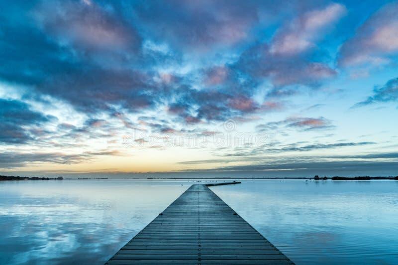 Gebogen pier in water stock afbeelding