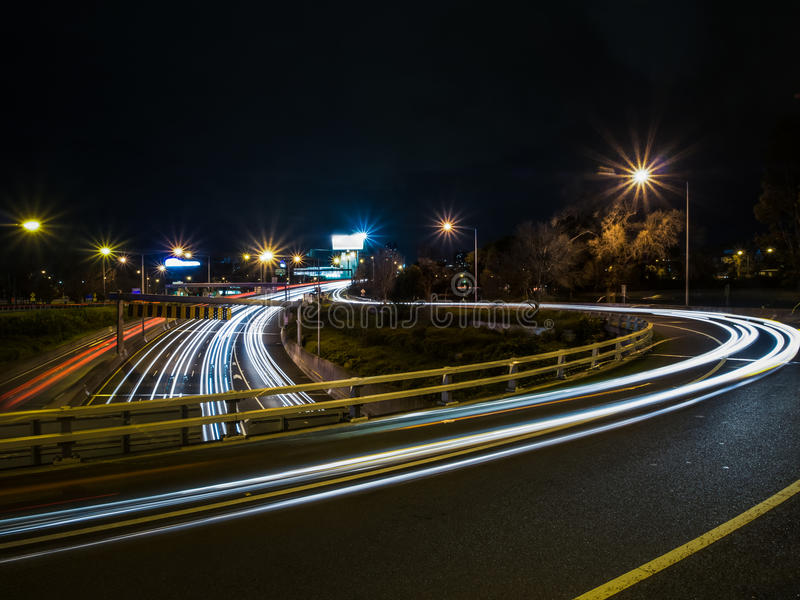 Gebogenes Licht schleppt in der Nacht stockbilder