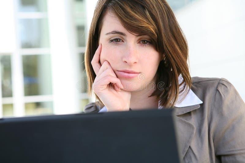 Gebohrte Frau auf Laptop-Computer lizenzfreies stockbild