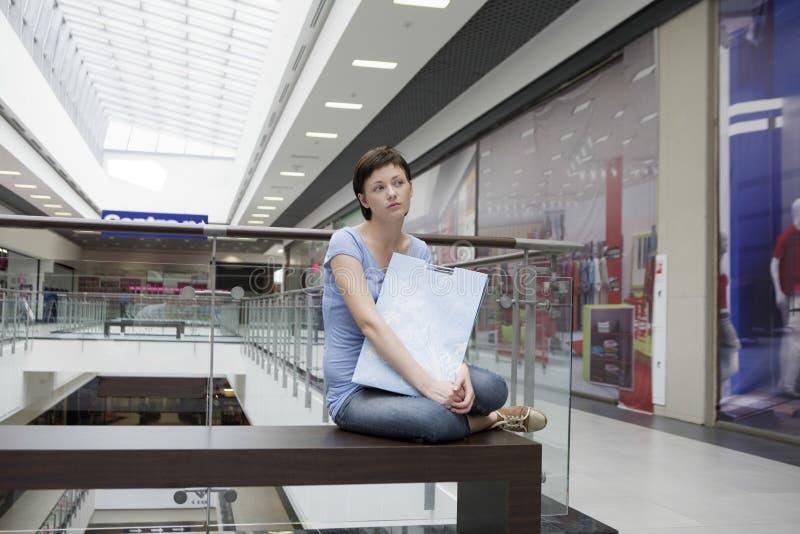 Gebohrte Frau mit der Papiertüte, die im Einkaufszentrum sitzt lizenzfreie stockfotografie