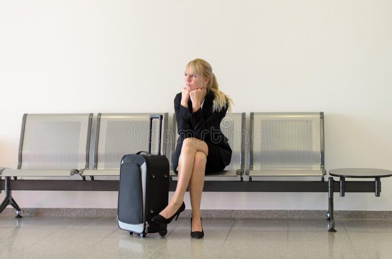 Gebohrte Geschäftsfrau, die auf einen Flug wartet stockfotografie