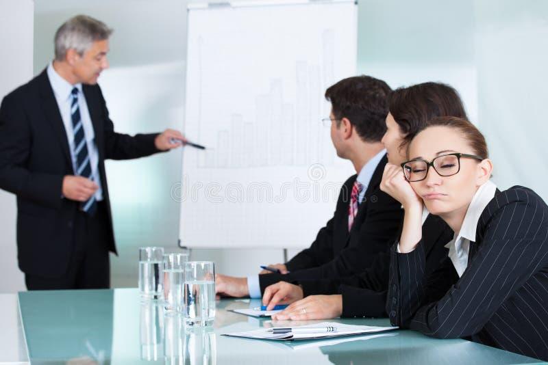 Gebohrte Geschäftsfrau, die in einer Sitzung schläft lizenzfreie stockbilder