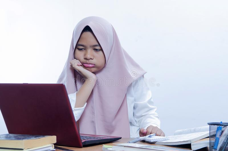 Gebohrte junge Frau im B?ro, das mit einem Laptop arbeitet stockfotografie