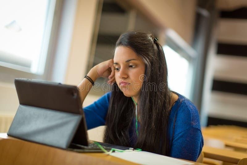 Gebohrte junge Studentin am Hochschulklassenzimmer Sie ` s unter Verwendung der Tablette und der Kopfhörer für das Nehmen von Ken stockfotografie