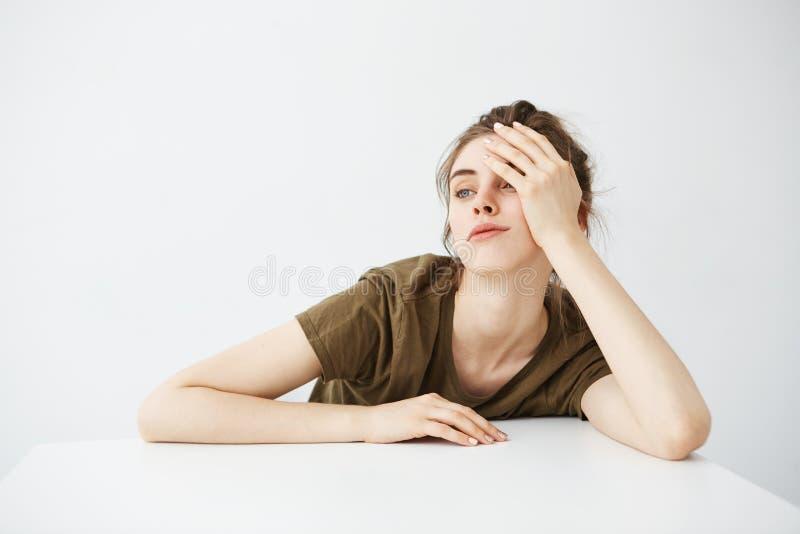 Gebohrte müde stumpfe junge Studentin mit dem Brötchen, das bei Tisch über weißem Hintergrund sitzt stockfoto