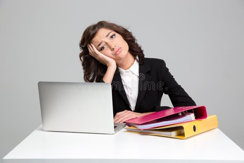 Gebohrte traurige junge Frau, die Laptop verwendet und mit Dokumenten arbeitet lizenzfreie stockbilder