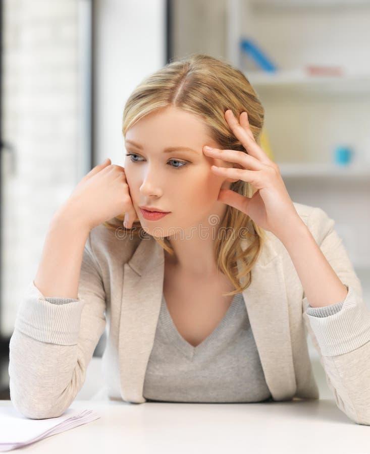 Gebohrte und müde Frau hinter der Tabelle stockbild