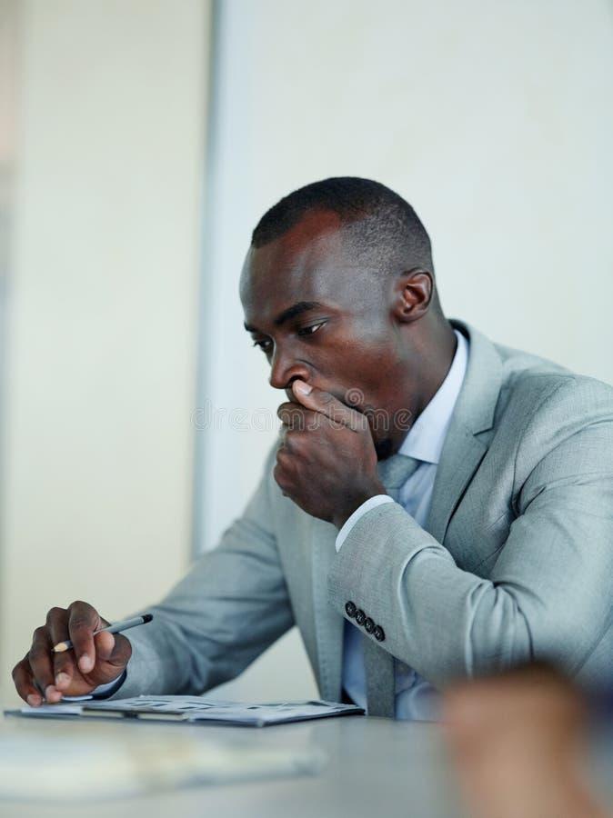 Gebohrter afrikanischer Geschäftsmann in der Sitzung lizenzfreie stockbilder