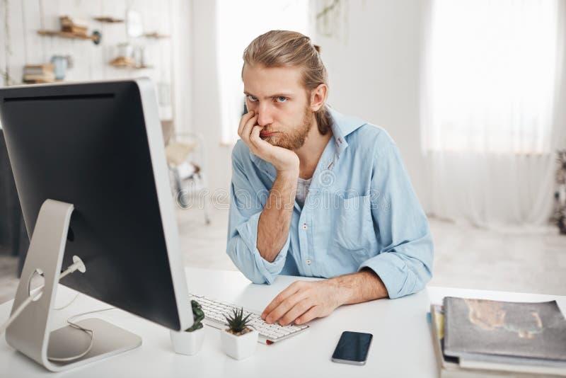 Gebohrter bärtiger kaukasischer Büroangestellter mit dem hoffnungslosen Blick, der Frist aber Ausfallung gegenüberstellt, um Beri stockfoto