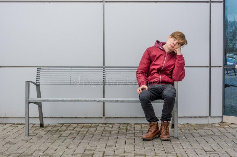 Gebohrter Jugendlicher, der auf der Bank im Freien in der Stadt sitzt stockbild