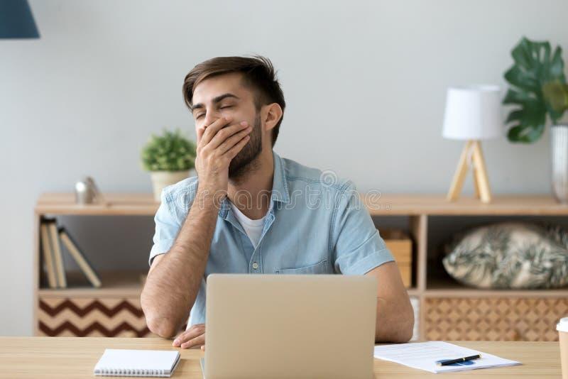 Gebohrter junger Mann, der am Schreibtisch sitzt stockfoto