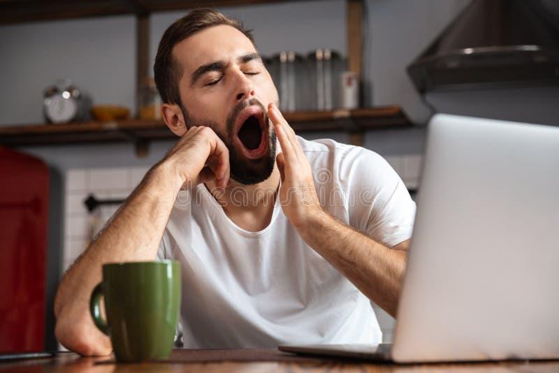 Gebohrter junger Mann unter Verwendung der Laptop-Computers stockbild
