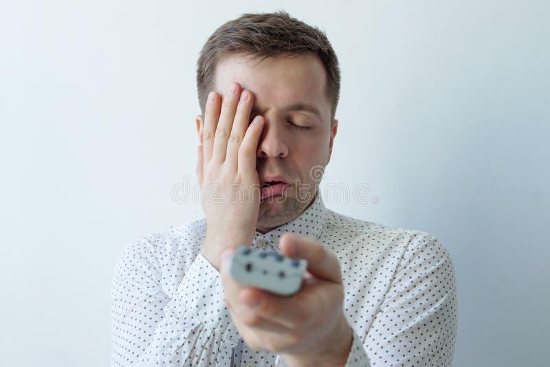 Gebohrter Mann, der fernsieht und schließend Gesicht mit der Hand zapping stockbild
