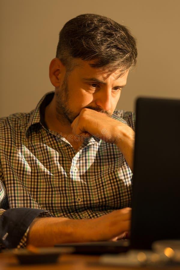 Gebohrter Mann, der Laptop verwendet stockbilder