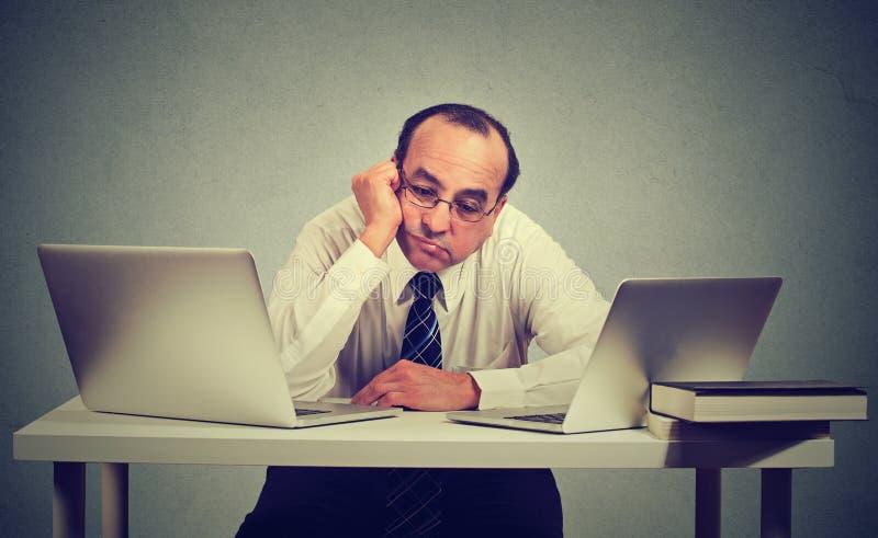 Gebohrter Mann, der vor zwei Laptop-Computer sitzt stockbilder