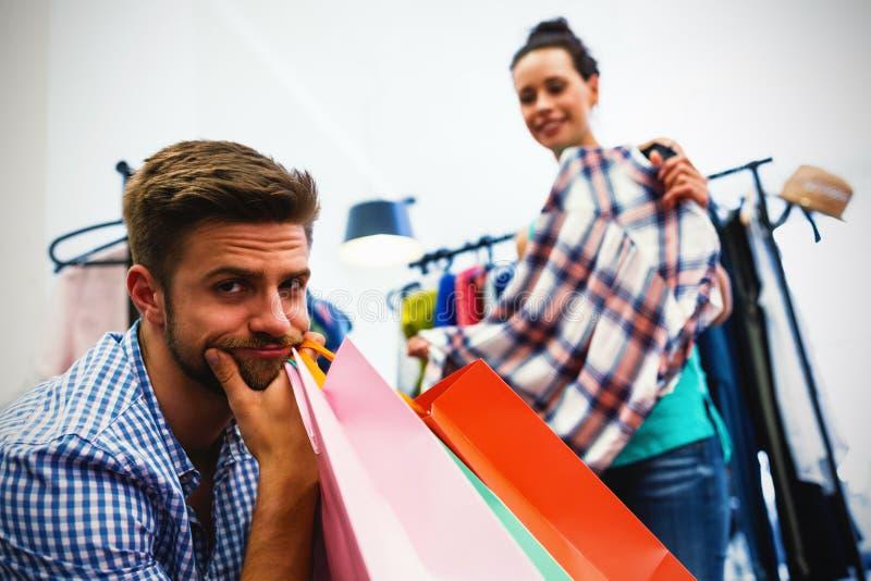 Gebohrter Mann mit Einkaufstaschen während Frau durch Kleiderständer stockfoto