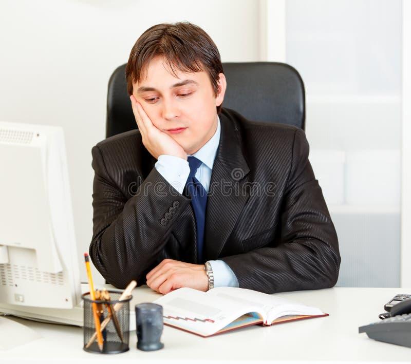 Gebohrter moderner Geschäftsmann, der am Schreibtisch im Büro sitzt lizenzfreies stockfoto