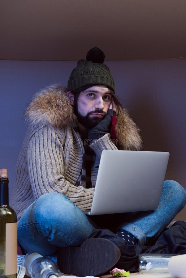 Gebohrter obdachloser Mann mit Laptop lizenzfreie stockfotos