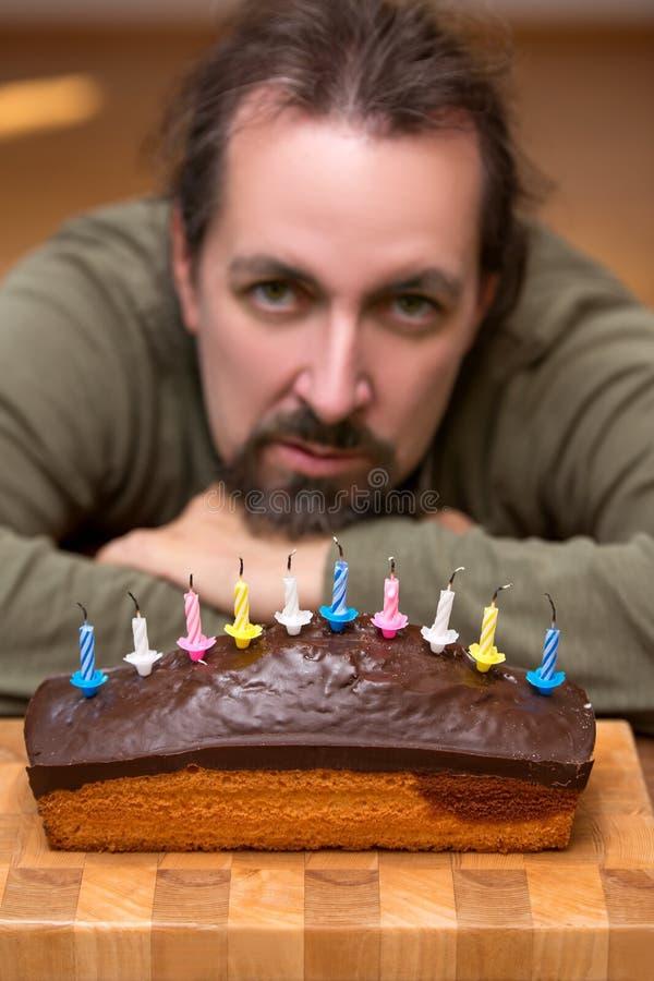 Gebohrter oder ärgerlicher schauender Mann hinter einem Marmorkuchen lizenzfreie stockfotos