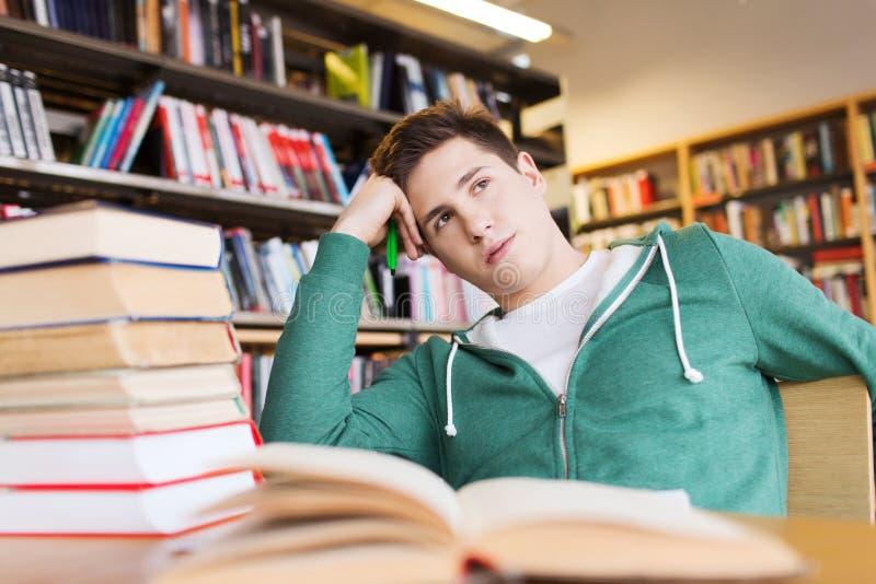 Gebohrter Student oder junger Mann mit Büchern in der Bibliothek lizenzfreies stockfoto