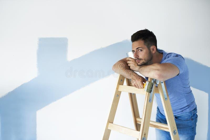Gebohrter und missfallener Mann, der einen Bruch von der Malerei fängt stockfotografie