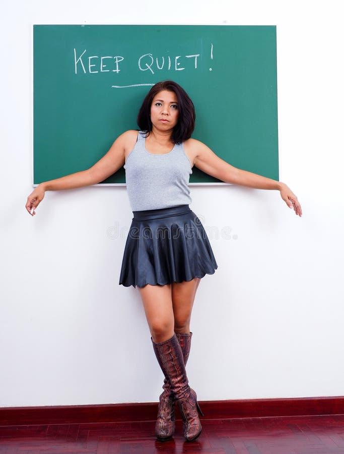 Gebohrter weiblicher Lehrer steht vor grüner Tafel stockbilder