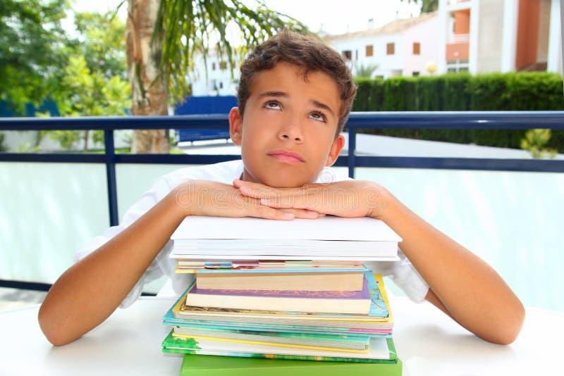 Gebohrtes Denken des Jungenkursteilnehmers Jugendlicher mit Büchern lizenzfreie stockbilder