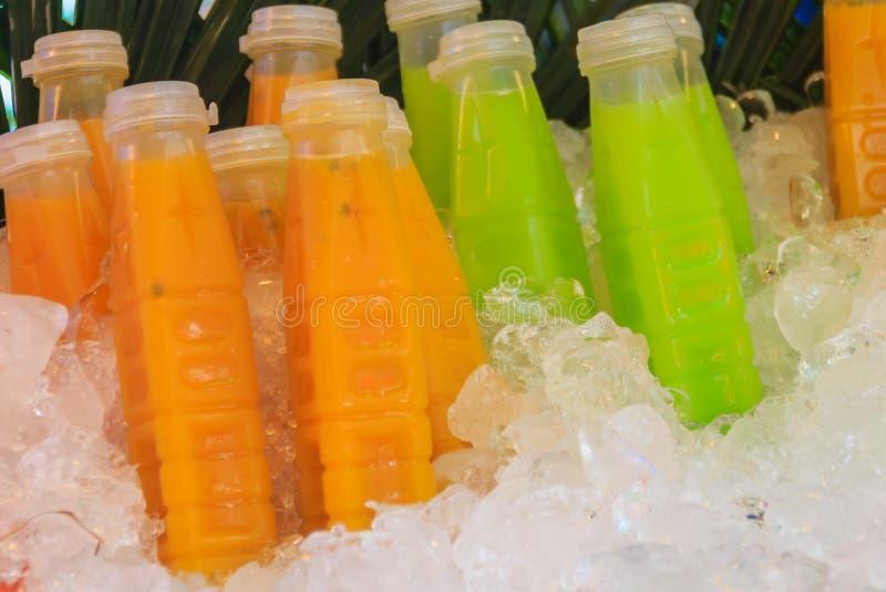 Gebotteld van passievrucht, guave, en mangosappen op ijsdoos wer stock afbeelding