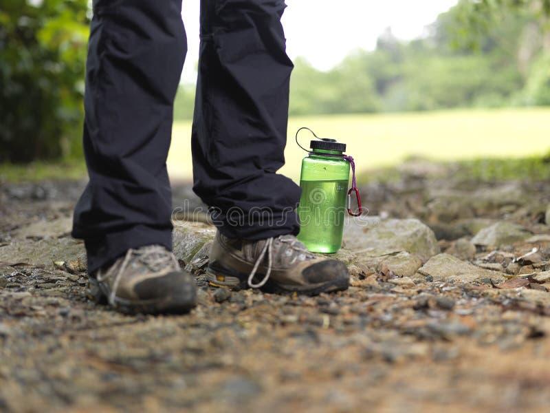Gebotteld water bij de voet voeten van trekker stock foto