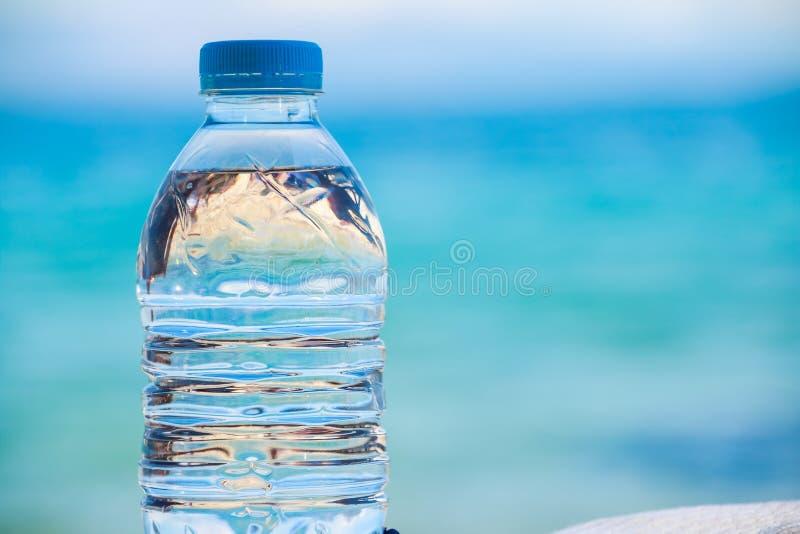 Gebotteld water op een hete dag bij het strand Plastic fles met duidelijk water, op overzeese achtergrond te drinken fles water  royalty-vrije stock afbeeldingen