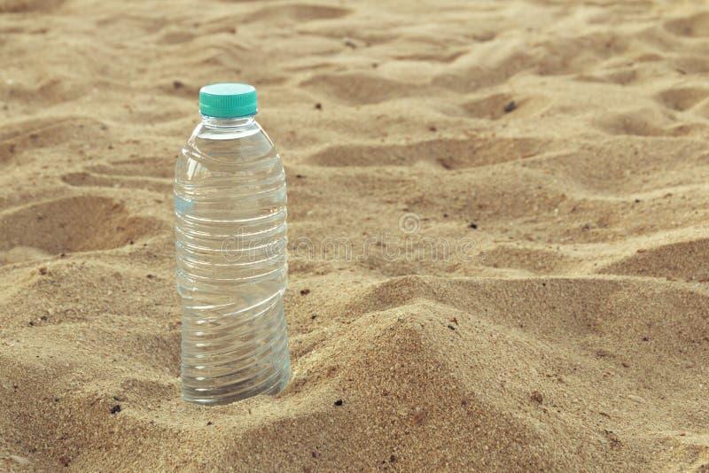 Gebotteld water op een hete dag bij het strand Plastic fles met duidelijk water, op overzeese achtergrond te drinken fles water  royalty-vrije stock fotografie