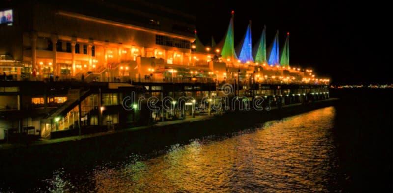 Gebouwen door rivier in stad bij nacht royalty-vrije stock afbeeldingen