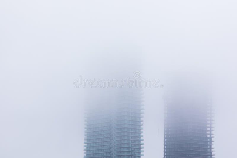 Gebouwen door wolken worden behandeld die royalty-vrije stock afbeelding