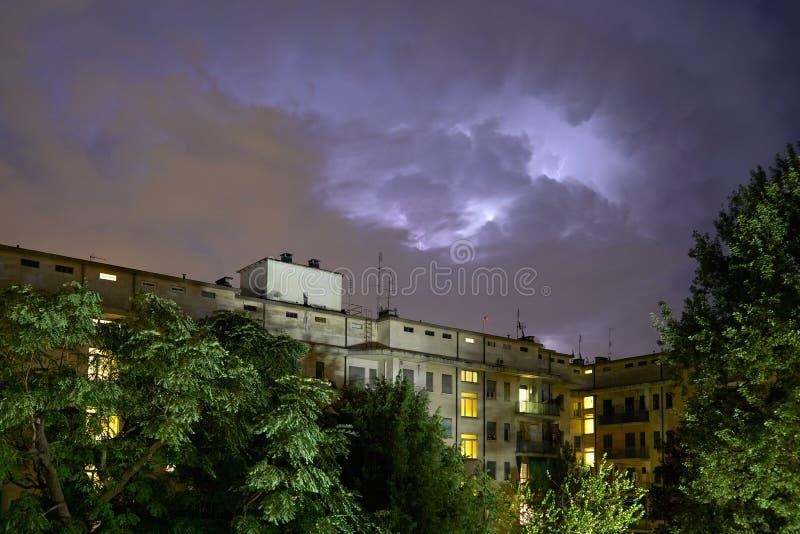 Gebouwen en groene bomen bij nacht, verlichte hemel tijdens een bliksemonweer stock fotografie