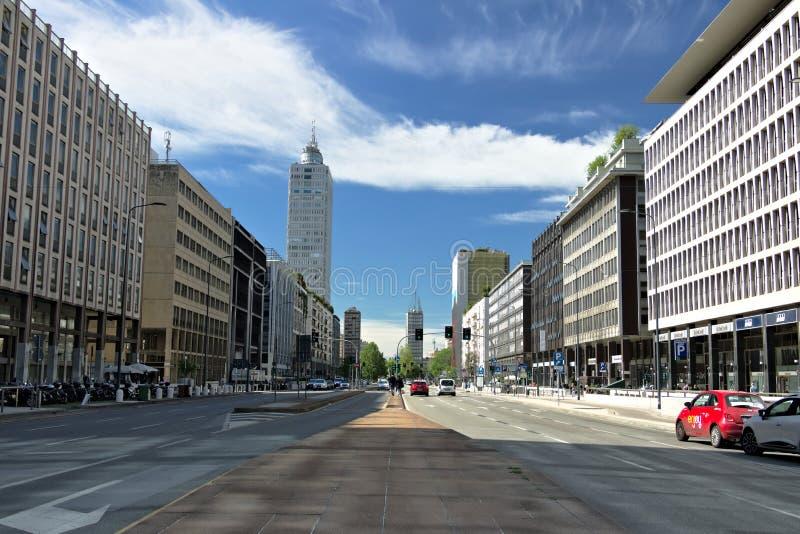 Gebouwen, wegen en verkeer in Milaan Rode auto, verkeer binnen via Vittor Pisani Blauwe Hemel met Wolken stock afbeeldingen