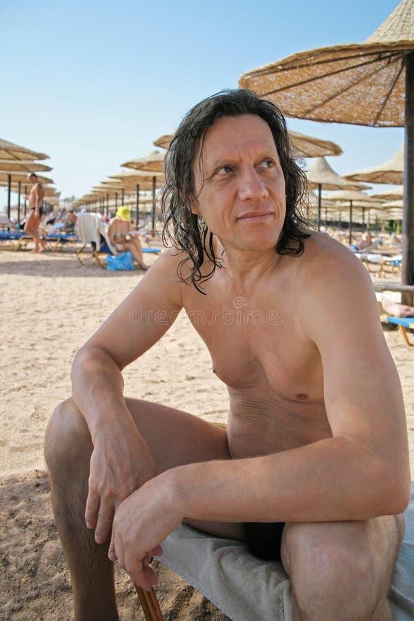 Gebräunt, ein älterer Mann, der auf dem Strand sitzt stockbilder
