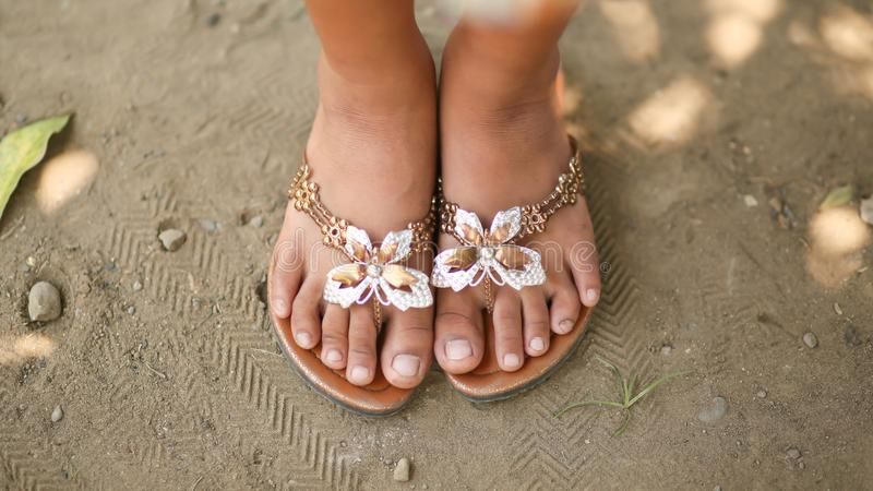 Gebräunte Beine eines kleinen Mädchens in den Schiefern mit einem dekorativen Schmetterling Mädchen barfuß in den Sommerschuhen a stockfotos