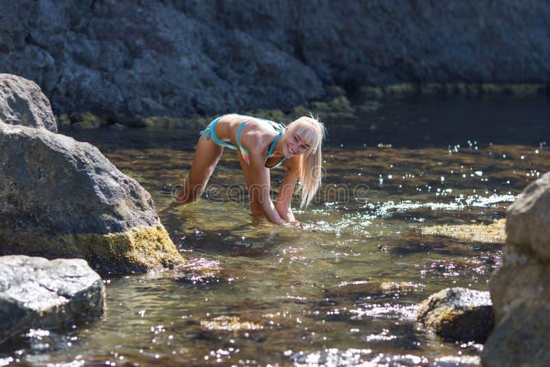 Gebräunte blonde behaarte weibliche Person, die an abgelegenem Ort der wilden felsigen Küste stillsteht stockbilder