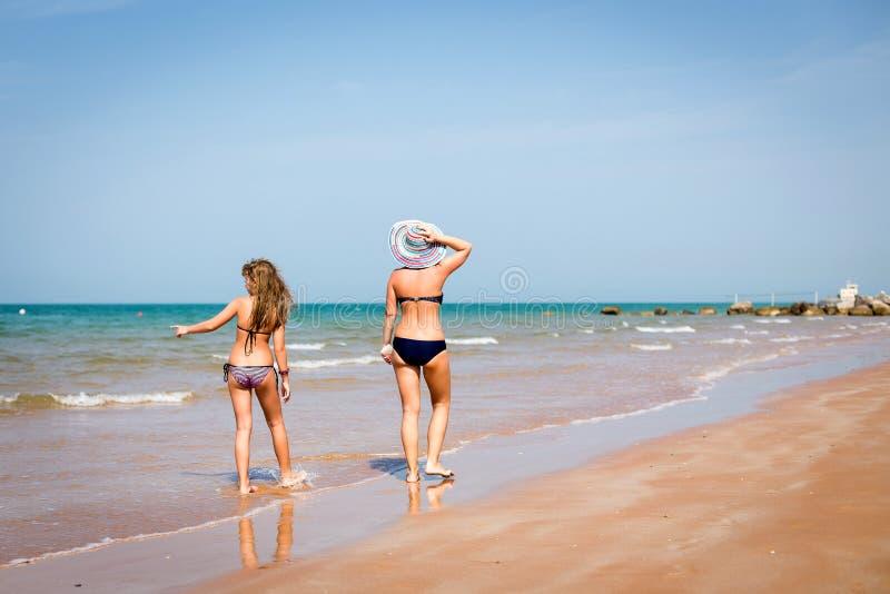 Gebräunte Frau und Mädchen, die auf den Strand geht stockfotos