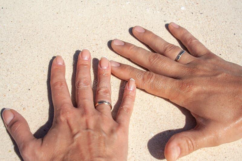 Gebräunte Hände von Jungvermählten mit Goldringen auf Ringfingern auf weißem Sand als Symbol der Hochzeit reisen stockfoto