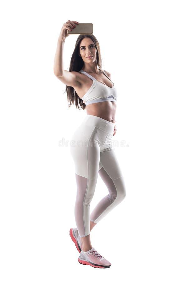 Gebräunte latino Schönheitseignungsfrau mit dem athletischen Körper, der selfie mit Handy nimmt lizenzfreies stockbild