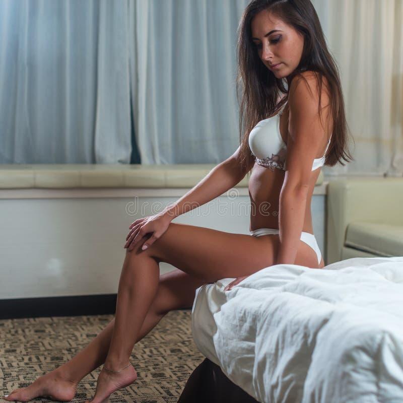 Gebräunter tragender weißer BH der dünnen jungen Brunettefrau, der das Sitzen auf Bett im hellen Schlafzimmer aufwirft stockfoto