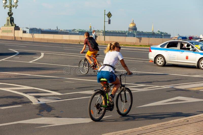 gebräuntes nettes kaukasisches Mädchen in einem weißen T-Shirt und kurze Hosen auf einem Fahrrad stockbild