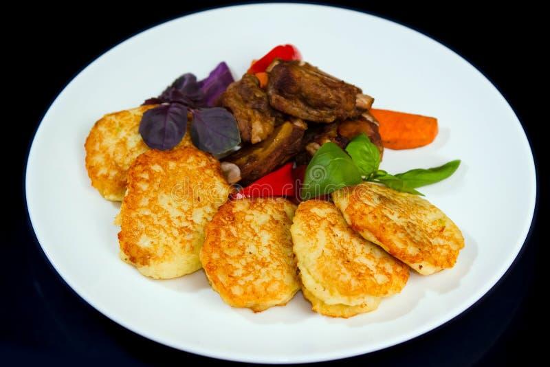 Gebraden aardappelpannekoeken, geroosterde varkensvleesribben, die met basilicum worden gediend, geroosterde wortelen en paprika stock afbeeldingen