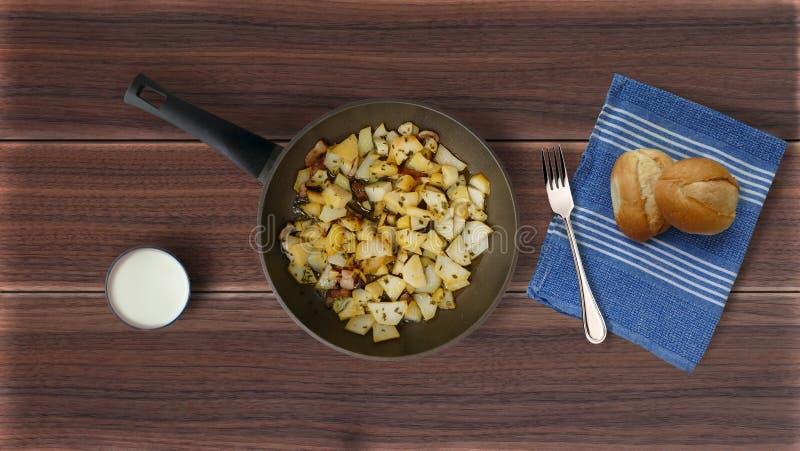 Gebraden aardappels in een gietijzerpan stock afbeeldingen