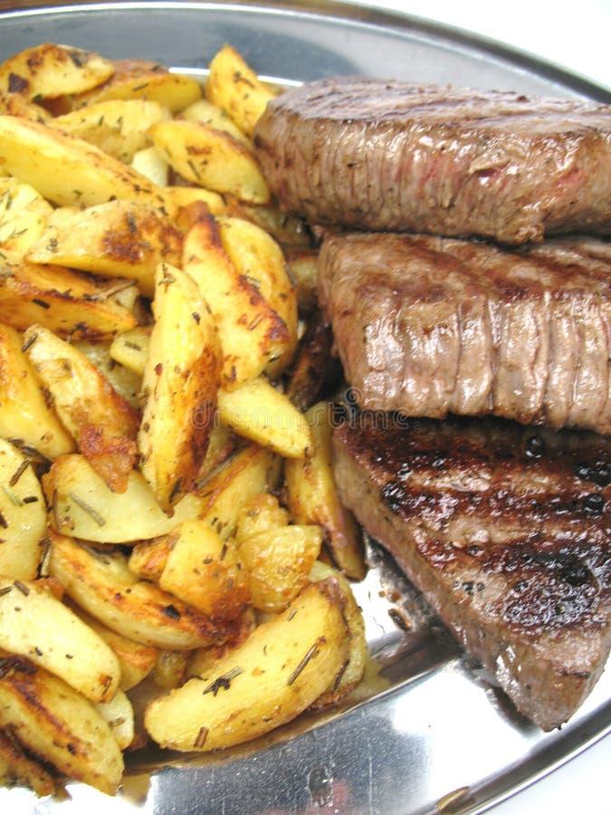 Gebraden aardappels en lapje vlees stock foto's