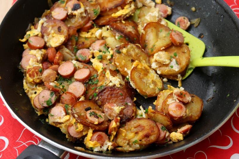 Gebraden aardappels met eieren en worst stock foto