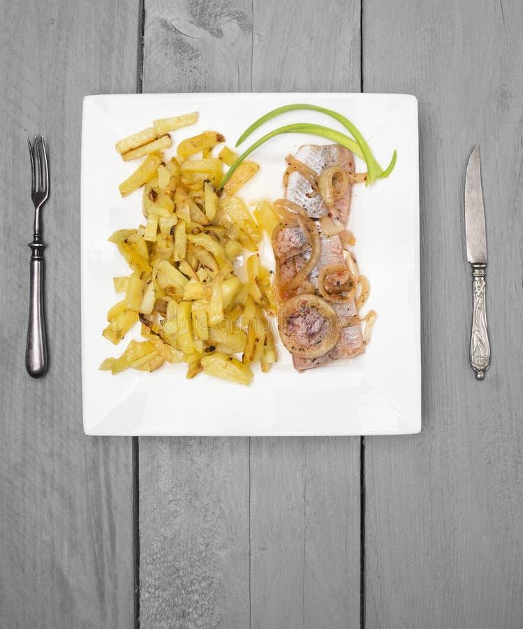 Gebraden aardappels met haringen en ui op grijze houten lijst stock afbeelding