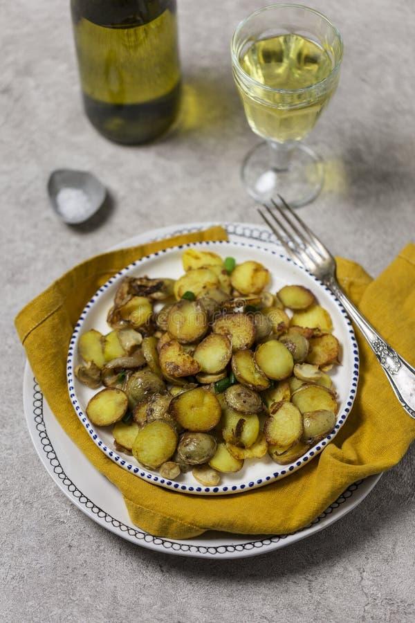 Gebraden aardappels met paddestoelen en ui in witte plaat met wijnstok bij grijze achtergrond voor vakantiediner stock foto