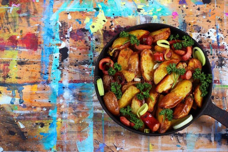 Gebraden aardappels met worsten, uiringen en groene peterselie Mea stock foto's